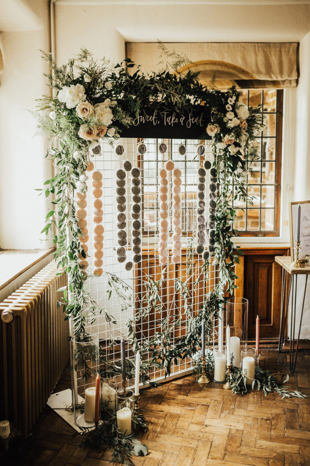 a wedding seating chart covered with greenery