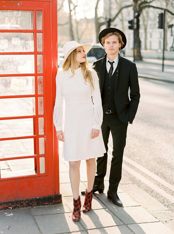 a 70s inspired knee wedding dress with a high neckline, long sleeves, a matching hat and plaid booties