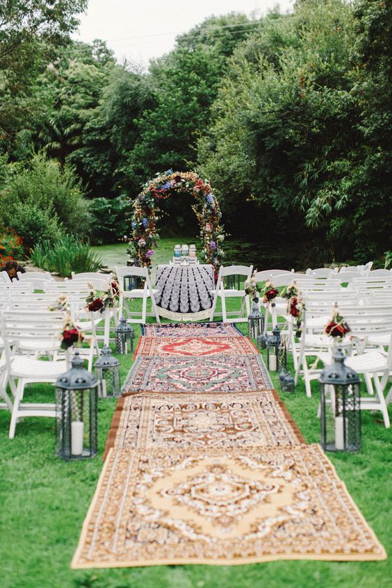 a boho 70s wedding ceremony space done with layered rugs, candle lanterns and a bold floral arch