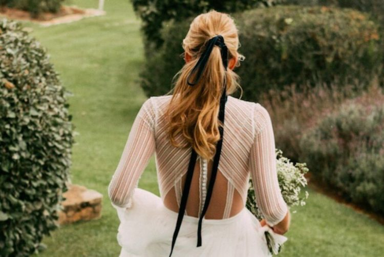 a wavy ponytail with a long black velvet ribbon that makes it chic and bold adding a twist to a simple hairstyle