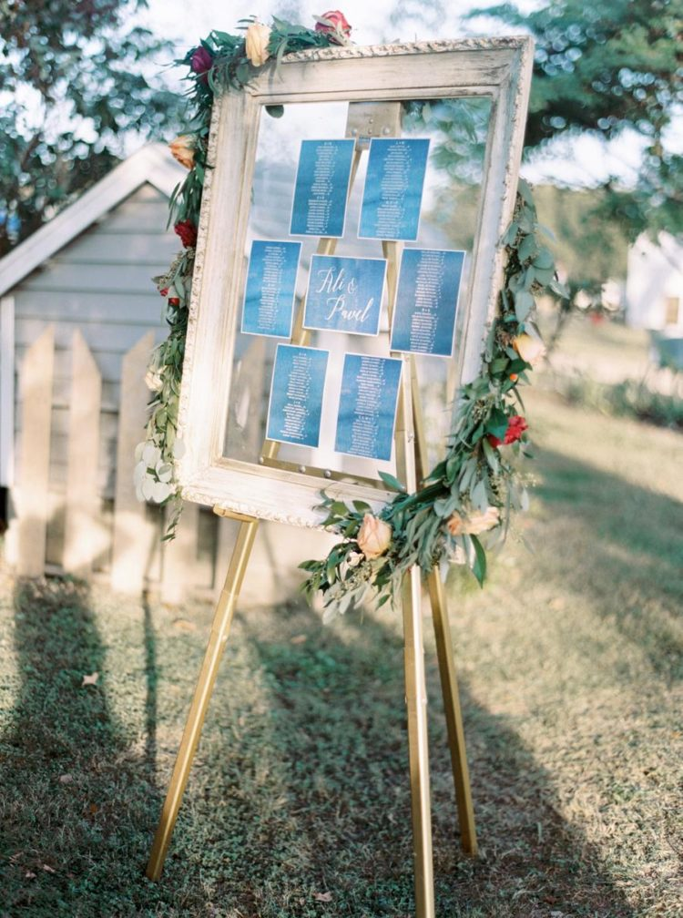 The wedding seating chart was done in navy and copper and decorated with greenery and bright blooms