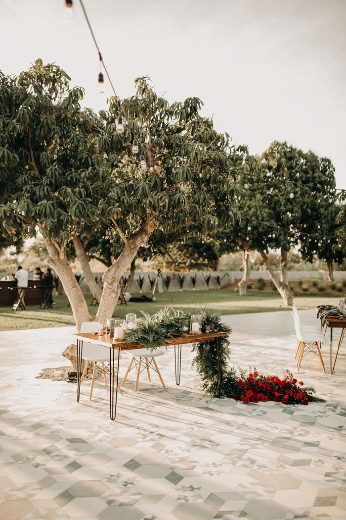 a lovely decorated sweetheart table under a tree