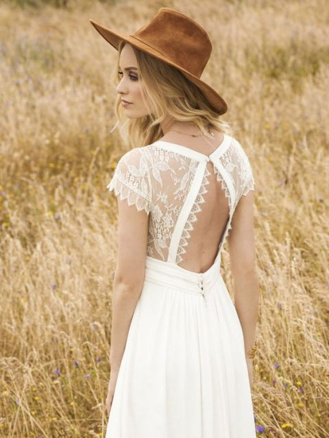 a boho wedding gown with a lace bodice and a cutout back on a button and a plain A-line skirt and a hat for a boho bride