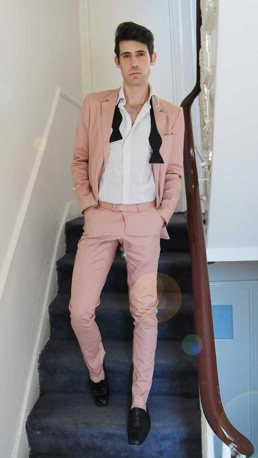 a pink suit, a white shirt, black shoes and a black bow tie for a fresh and cool summer groom's outfit
