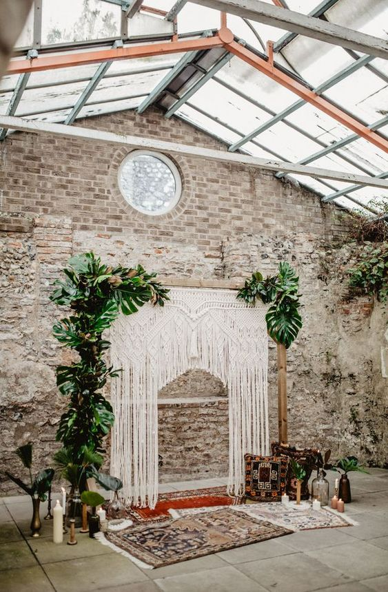 a tropical 70s inspired wedding ceremony space with a macrame and tropical leaf arch, bottles, candles and rugs