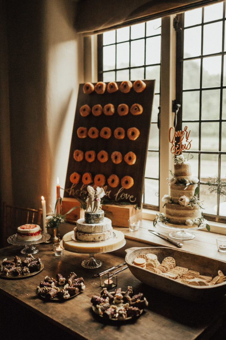 a wedding dessert table with a donut wall
