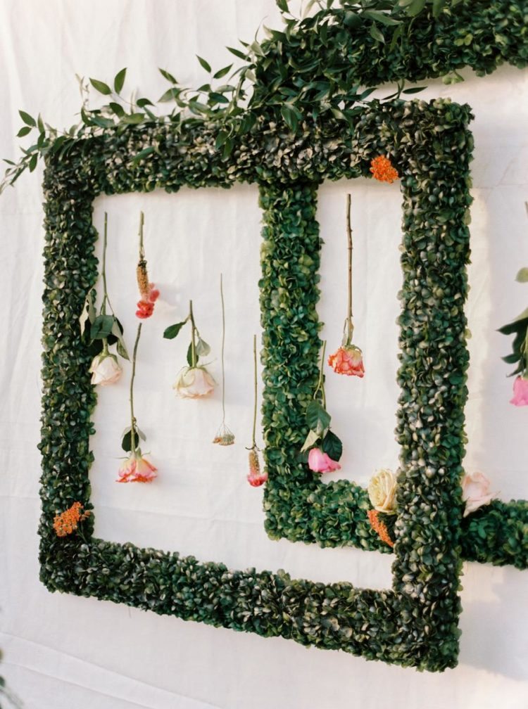 What a pretty wedding decoration of greenery frames with flowers hanging down