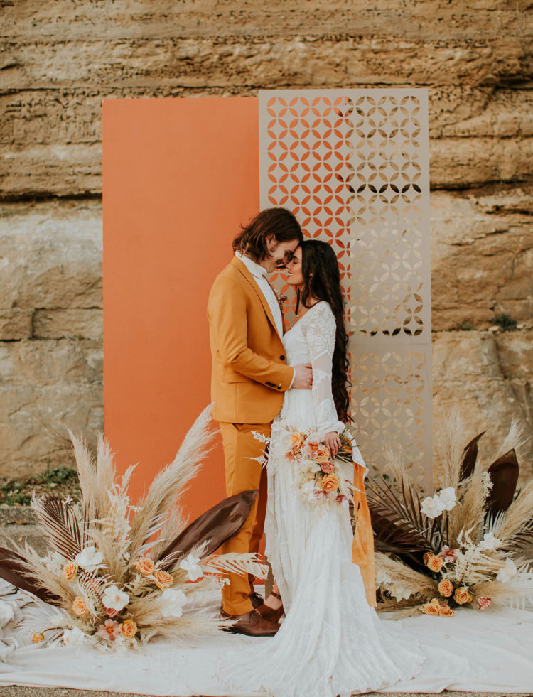 a creative 70s inspired wedding backdrop of an orange and a neutrla laser cut screen, dried fronds, leaves and blooms