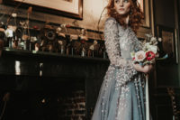 10 a grey A-line wedding dress with long sleeves, a high neckline and blush floral appliques