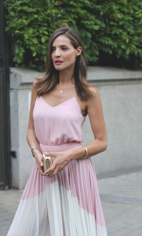 a pink spaghetti strap top, a color block pink and white pleated midi skirt and a tiny metallic clutch