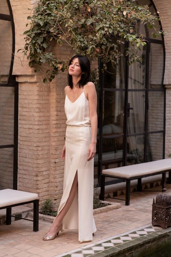 a white silk slip wedding dress with a side slit and vintage-inspired sparkling shoes for a casual bride
