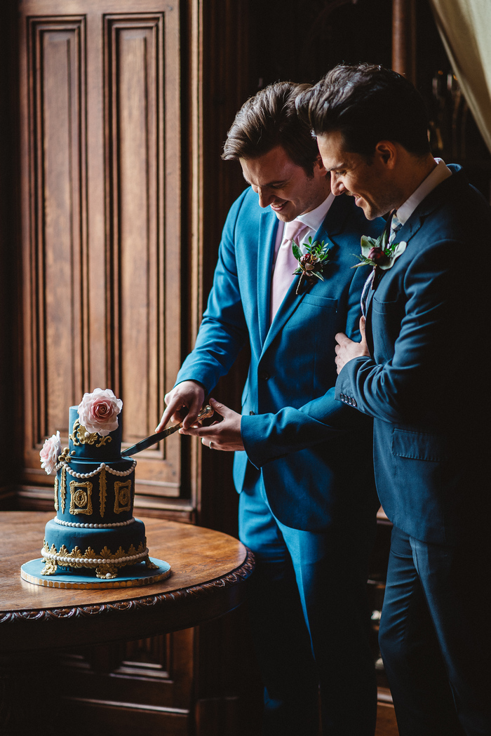 The wedding cake was bright blue, with gold and white decor plus beautiful pink roses
