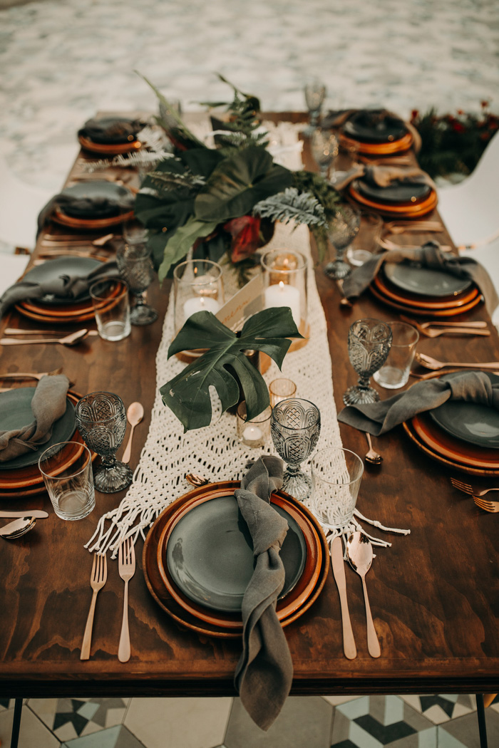 The wedding tablescapes were done with macrame runners, tropical leaves and greenery, copper and grey plates and grey glasses