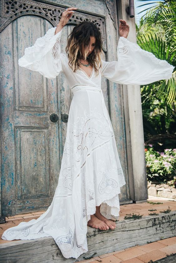 a boho lace and plain A-line wedding dress with bell sleeves, a high low skirt, a train and a deep neckline