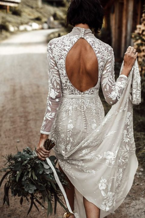 a gorgeous lace sheath wedding dress with a turtleneck, long sleeves and a cutout back on buttons plus a train