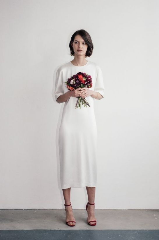 a white plain wedding dress of silk with short sleeves and a high neckline plus red heels for an accent