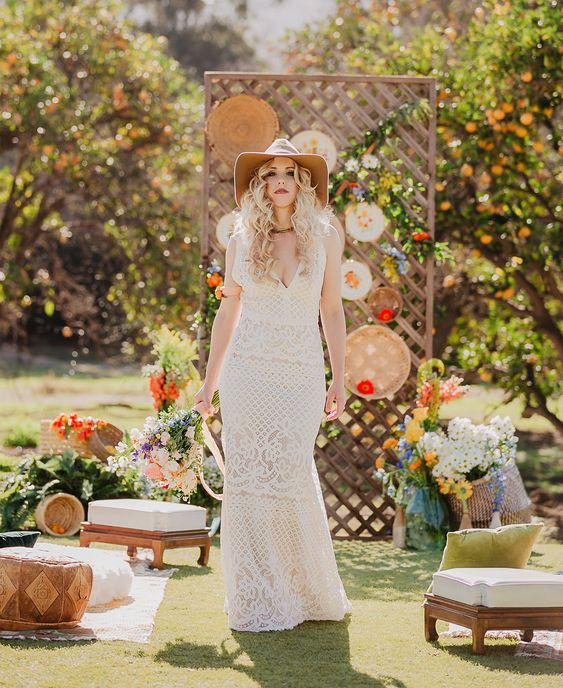 a boho lace sleeveless sheath wedding dress with a deep neckline paired with a neutral hat for a hippie feel