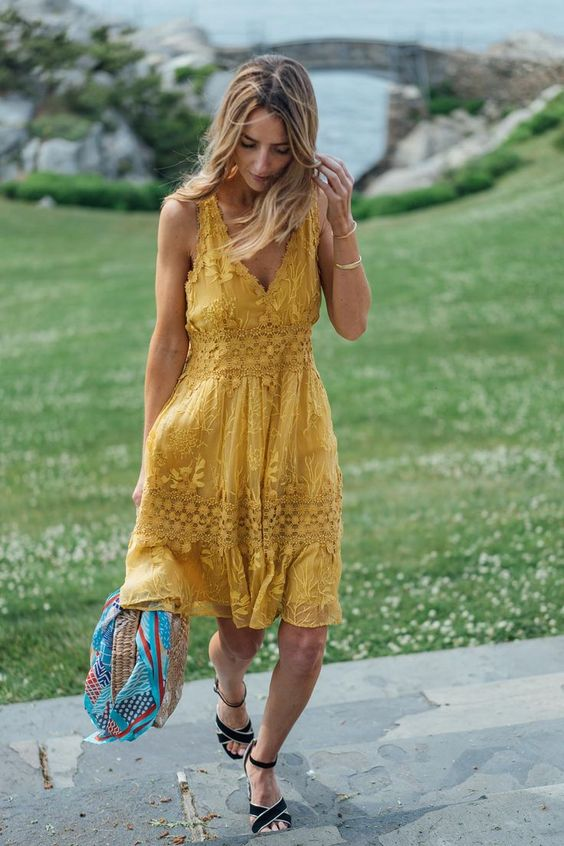a yellow lace knee dress on thick straps, with a V-neckline, black strappy shoes and a wicker hat for a summer wedding