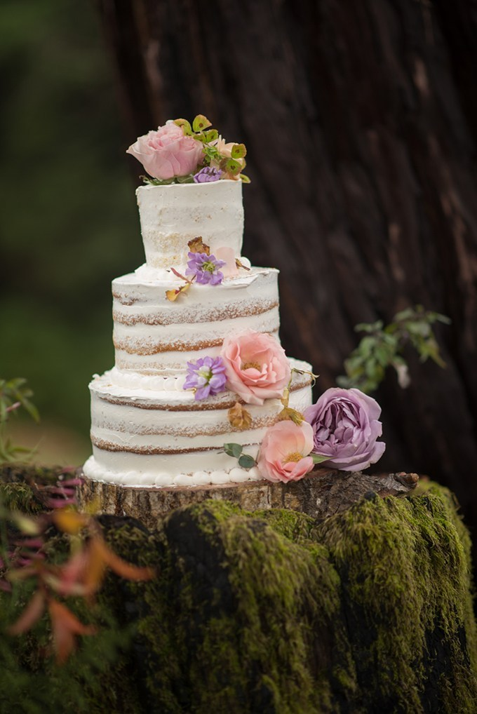 The wedding cake was naked and topped with large colorful fresh blooms