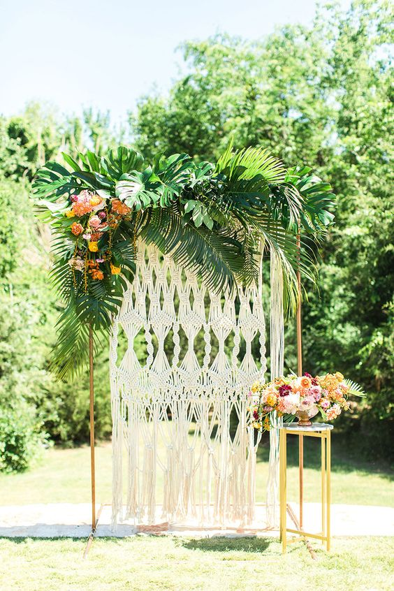 a bold 70s tropical wedding backdrop with torpical leaves, blooms, a macrame backdrop and lush florals