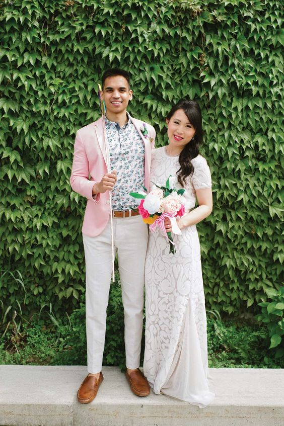 a bright summer groom's look with a floral shirt, a pink jacket, neutral pants, brown moccasins and a belt
