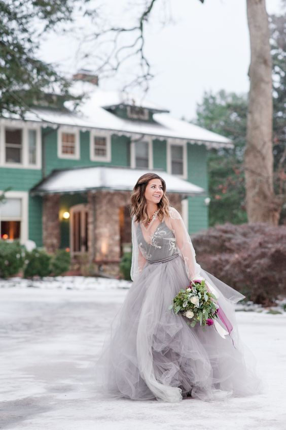 a grey wedding dress with a layered tulle skirt, an embroidered bodice and a sheer coverup with long sleeves