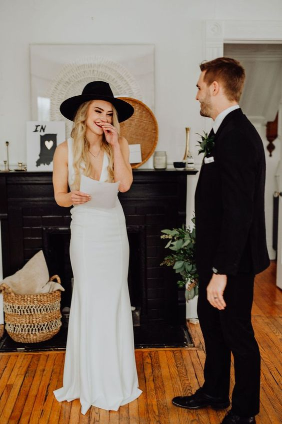 a plain sheath wedding dress with thick straps and a deep plunging neckline plus a black hat to finish off the look