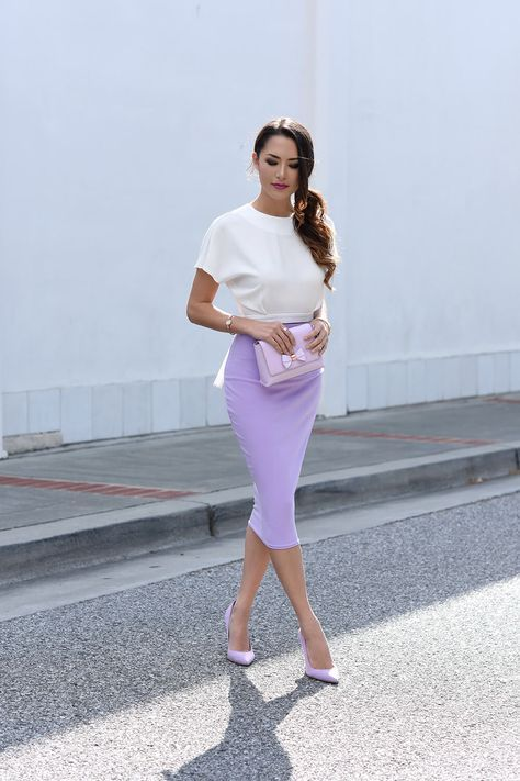 a white tee, a lavender pencil midi skirt, matching heels and a blush bag with a bow for a spring or summer wedding