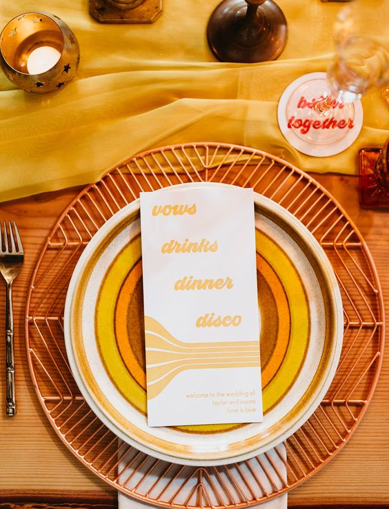 a bright wedding place setting with a woven charger, colorful plates, a bold menu, a yellow runner and some candles