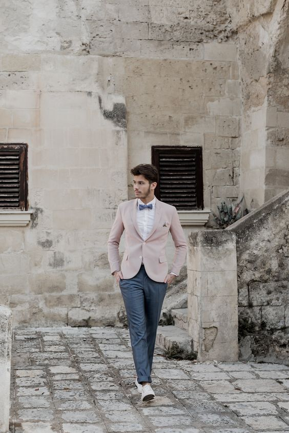 a gorgeous groom's look with graphite grey pants and a bow tie, a white shirt, a pink jacket and neutral shoes