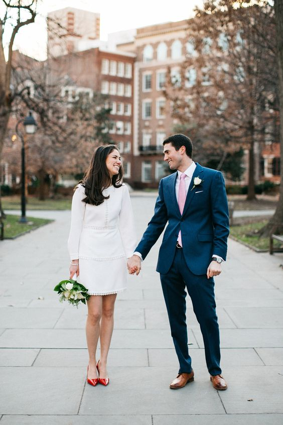 a mid-century modern short plain wedding dress with pompoms, long sleeves and red shoes as an accent