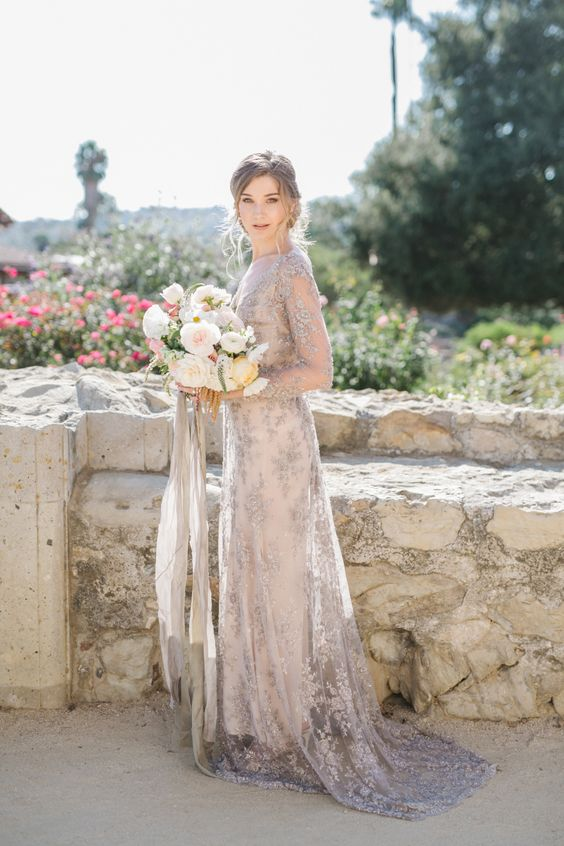 an embellished grey lace A-line wedding dress with a high neckline, long sleeves and a train for a glam bride