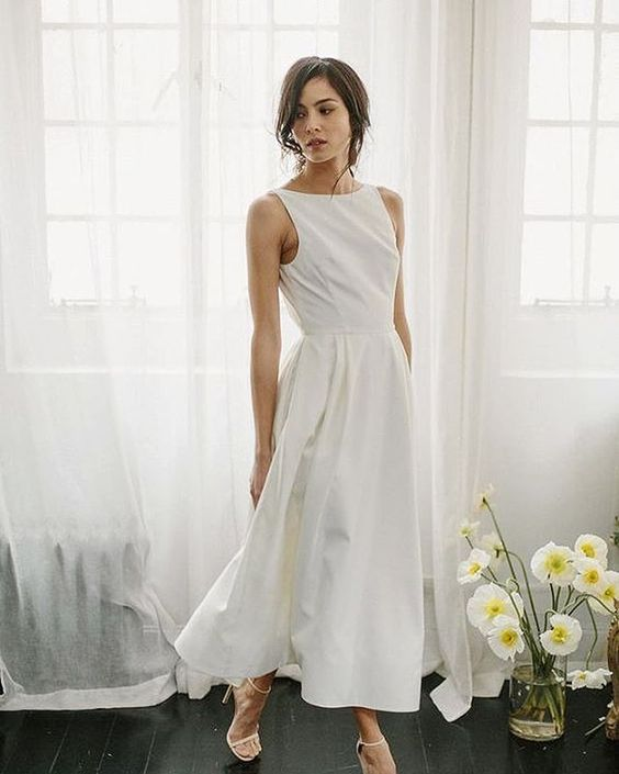 a sleeveless plain midi wedding dress with a pleated skirt and nude heels are a timeless combo for a casual bride