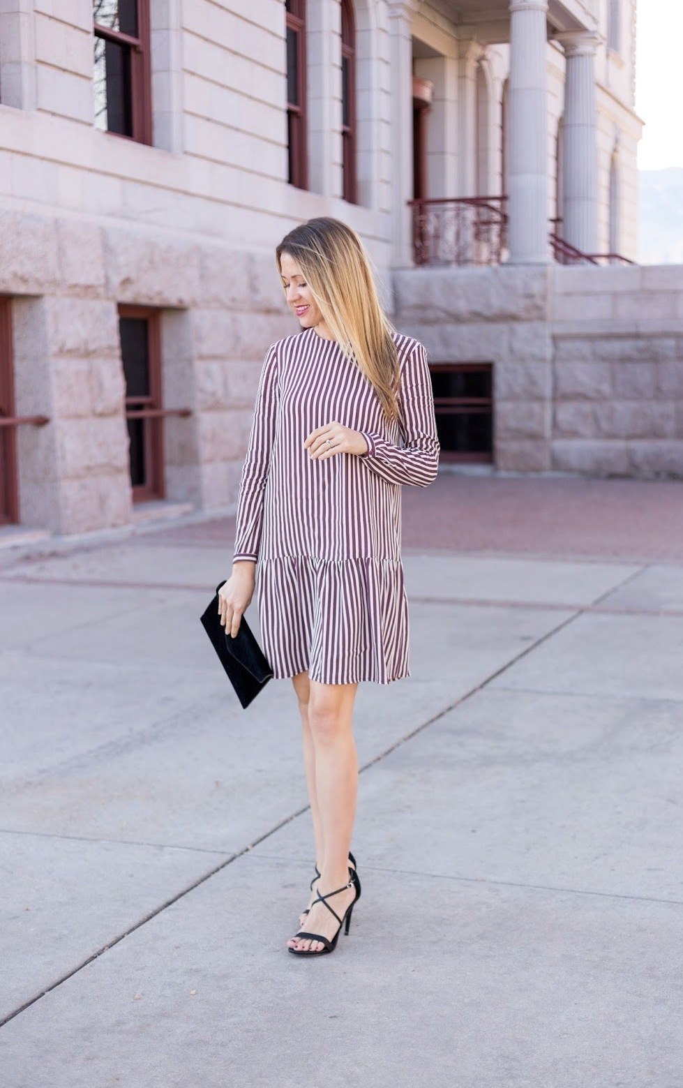 a striped burgundy and white drop waist over th eknee dress, black strappy shoes and a black velvet clutch for a fall wedding