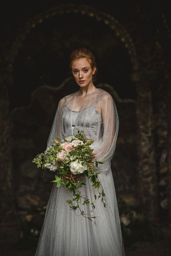 a vintage inspired grey silk wedding dress wtih an embellished skirt and an embellished cape with long sleeves