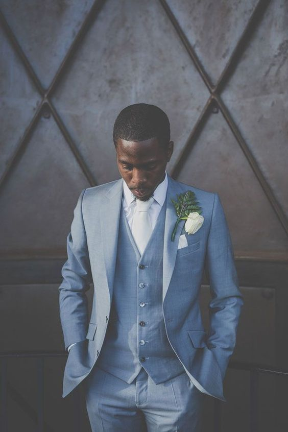 a formal groom's look with a blue three piece suit, a white shirt and a tie plus a whimsical boutonniere