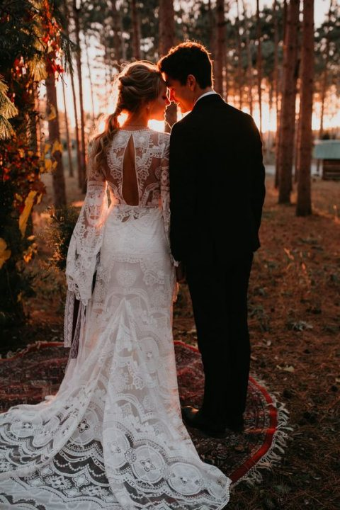 a romantic lace mermaid wedding dress with a cutout back, bell sleeves and a train for a boho bride