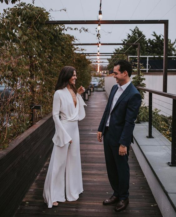a casual white bridal jumpsuit with a draped bodice, bell sleeves and bell pants for a 70s feel