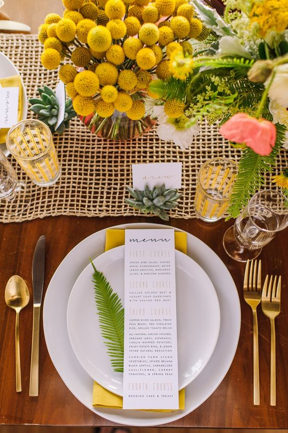 a colorful wedding tablescape with ferns, billy balls, a yellow mesh table runner, succulents, gold touches and blooms