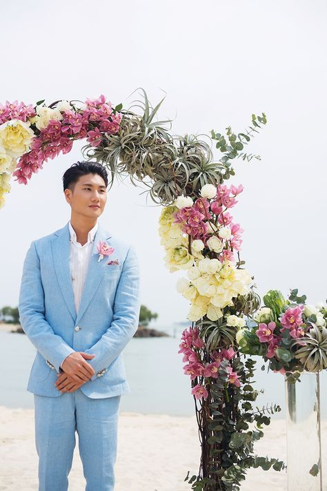 a serenity blue wedding suit with a white shirt and a pink floral boutonniere for a cool tropical groom's look