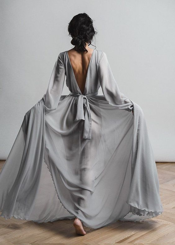a simple and romantic wedding dress in grey, with a cutout back, long sleeves and a sash