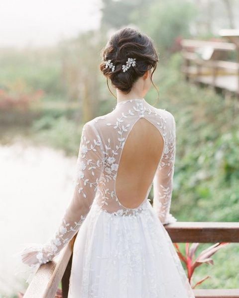 a very romantic A-line wedding dress with a sheer lace bodice and cutout back plus a full skirt and matching floral hairpieces