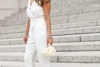 18 a casual white bridal jumpsuit with a V-neckline and a wrap top, nude heels and a statement bracelet