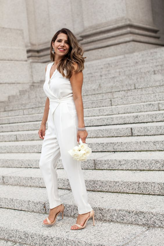 a casual white bridal jumpsuit with a V-neckline and a wrap top, nude heels and a statement bracelet