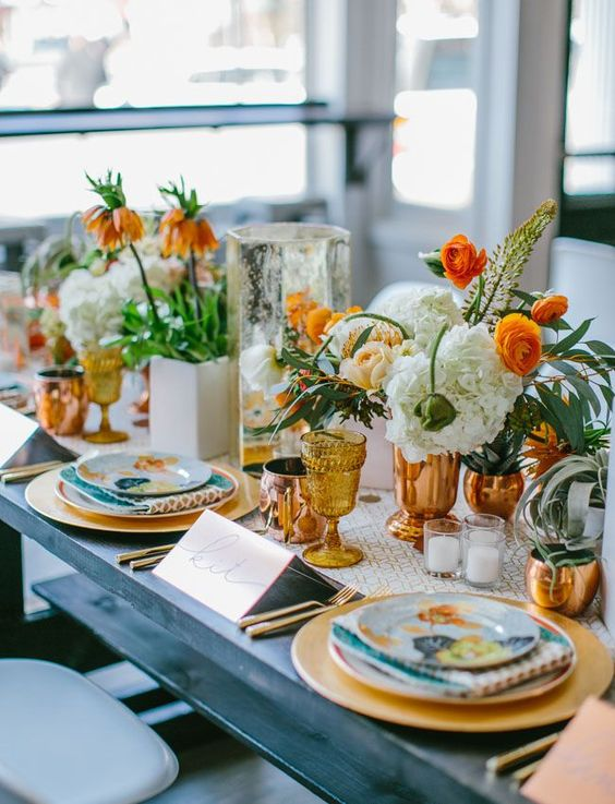 a colorful 70s wedding tablescape done with turquoise, gold and white details, lush florals and candles
