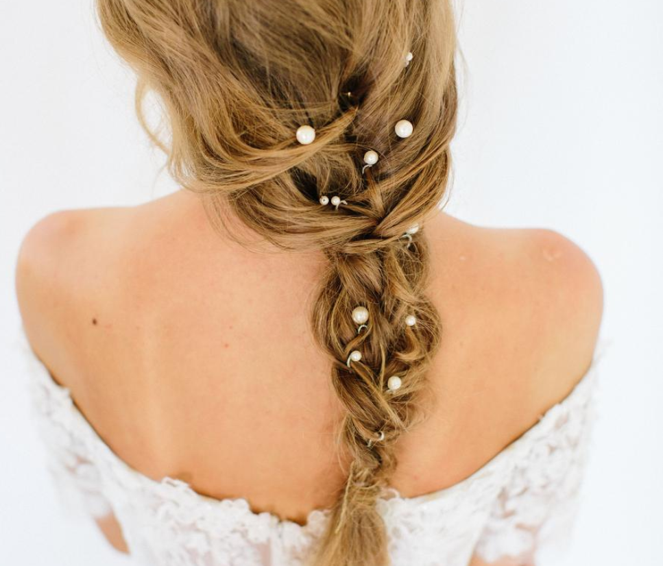 a messy bridal braid spruced up with pearl pins is a very chic and romantic idea