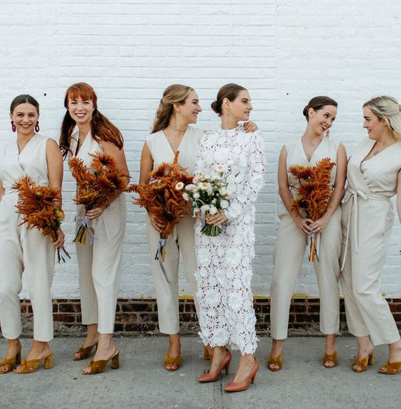 casual sleeveless off white jumpsuits, statement earrings and mustard mules for a modern wedding
