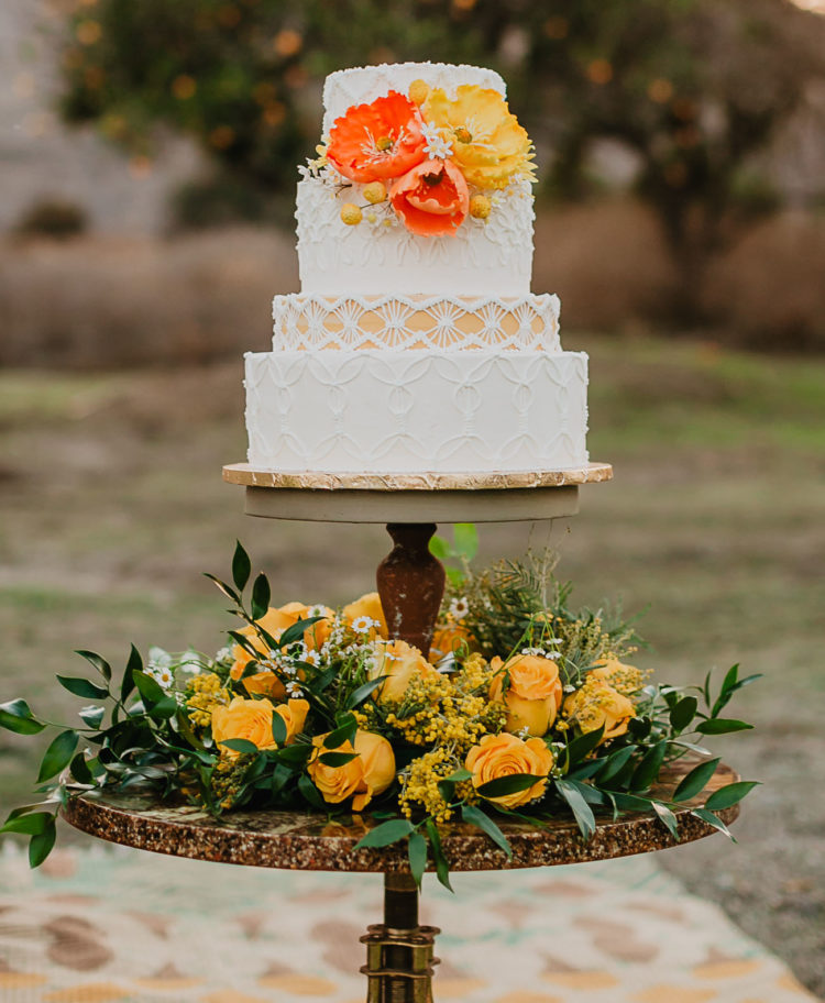 a bold 70s inspired wedding cake with various patterns, bold sugar blooms and served on a stand with blooms