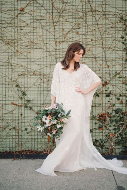 a lace sheath wedding dress with bell sleeves, a train, a V-neckline for a boho 70s inspired bridal look
