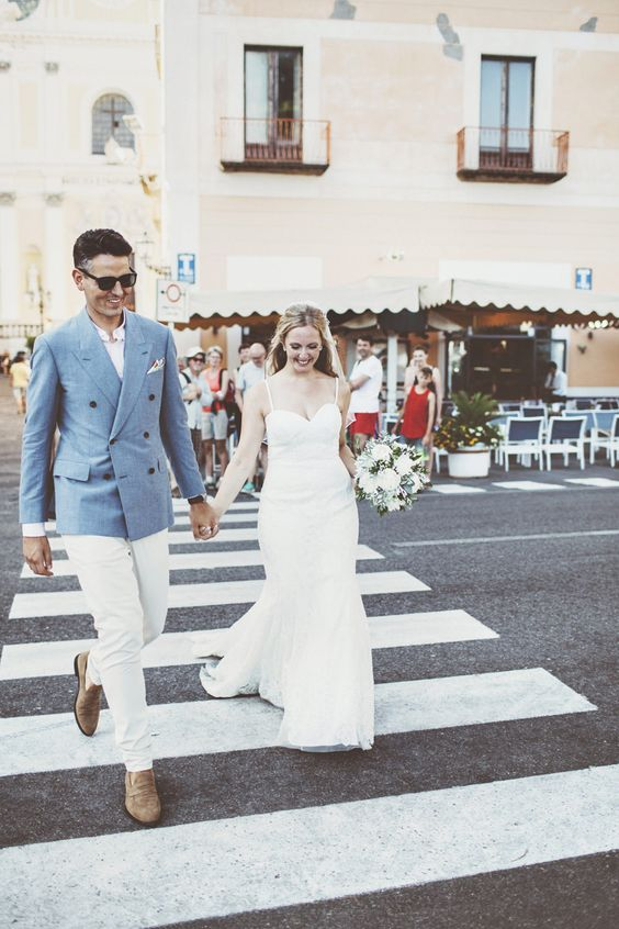 a stylish groom's outfit with a blue jacket, a white shirt and pants and brown moccasins for a coastal Italian wedding